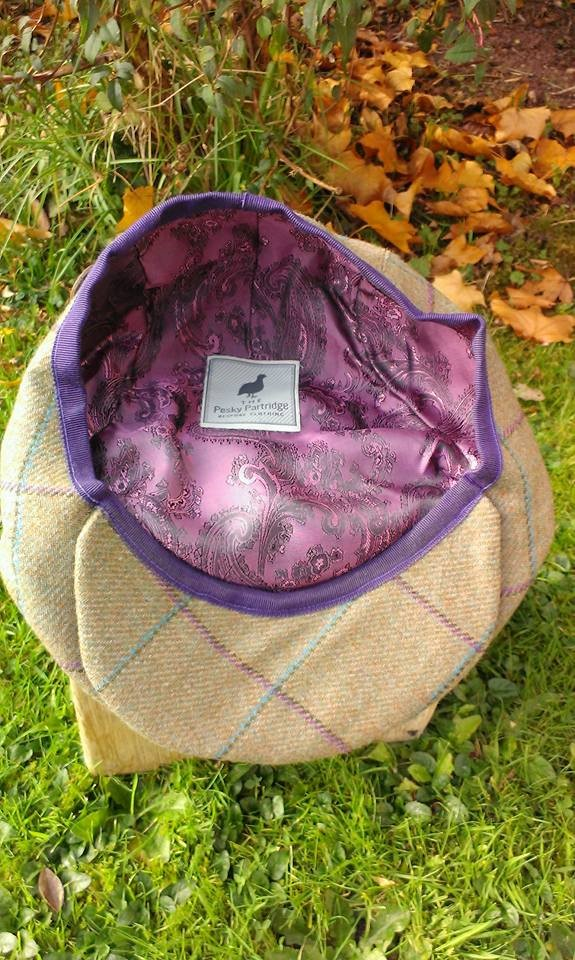 Tweed flat cap with purple and teal check showing purple lining