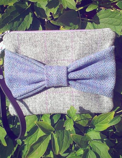 Tweed grey clutch bag with purple bow.