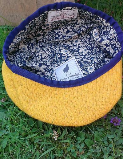 Mustard yellow Harris tweed flat cap with navy trim.